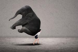Businesswoman lifting heavy elephant
